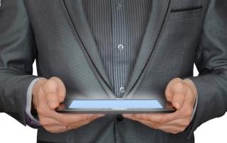 Photo gros-plan d'un homme d'affaires tenant une tablette mobile, pour illustrer l'article de blog qui explique aux PME et artisans au Luxembourg pourquoi ils ont besoin d'un site internet.
