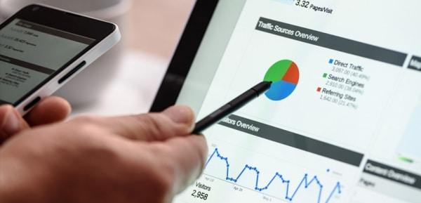 Photo montrant une personne avec un stylo qui analyse les sources de trafic d'un site e-commerce Prestashop.